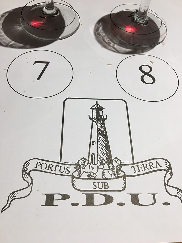 the bottoms of two wine glasses on a tasting mat bearing the seal of the P.D.U., a lighthouse with the motto PORTUS SUB TERRA