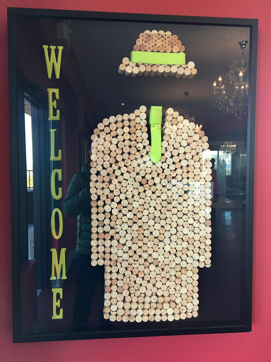 A WELCOME sign with the shape of a jacket and hat made of corks and a bit of green ribbon