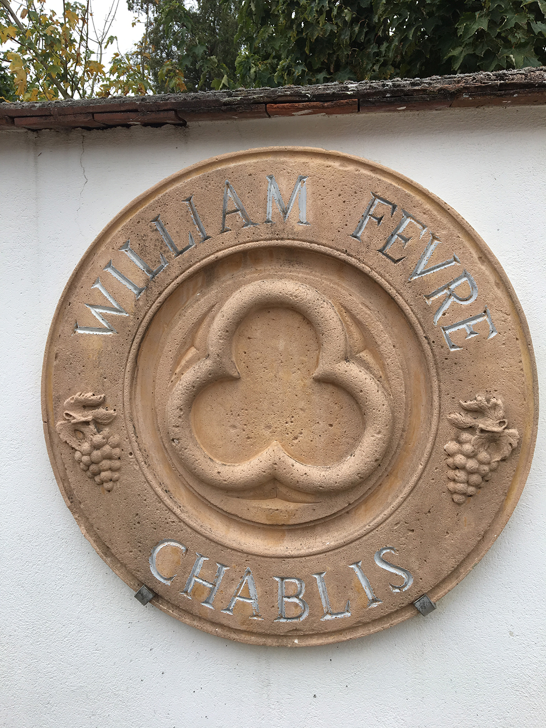 Circular William Fèvre relief plaque on wall