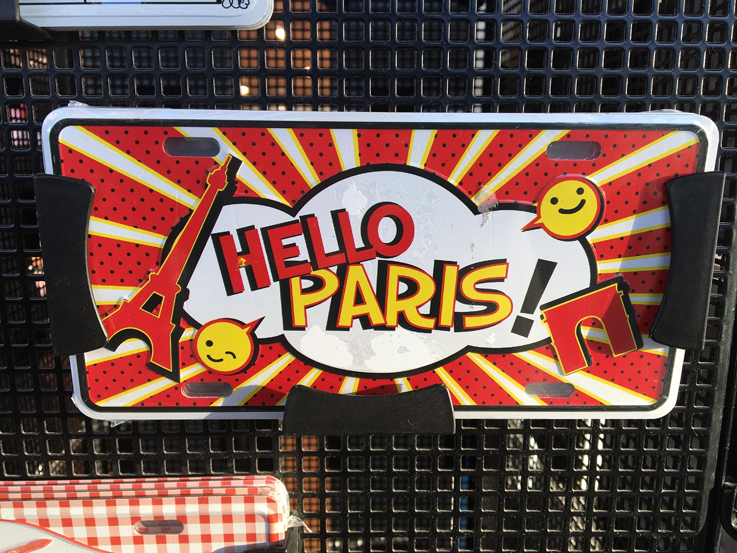 HELLO PARIS souvenir license plate with a garish red-and-yellow sunburst, silhouettes of the Eiffel Tower and the Ard de Triomphe, and two smiling cartoon speech balloons for no good reason at all