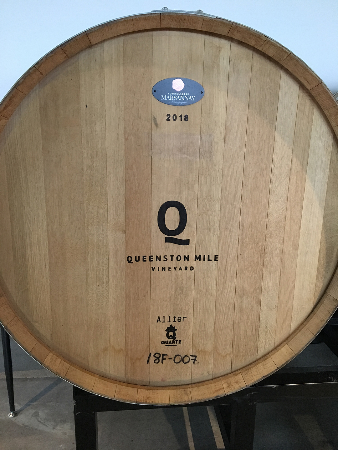 the end of a large barrel with the branding 'Queenston Mile Vinyeard'