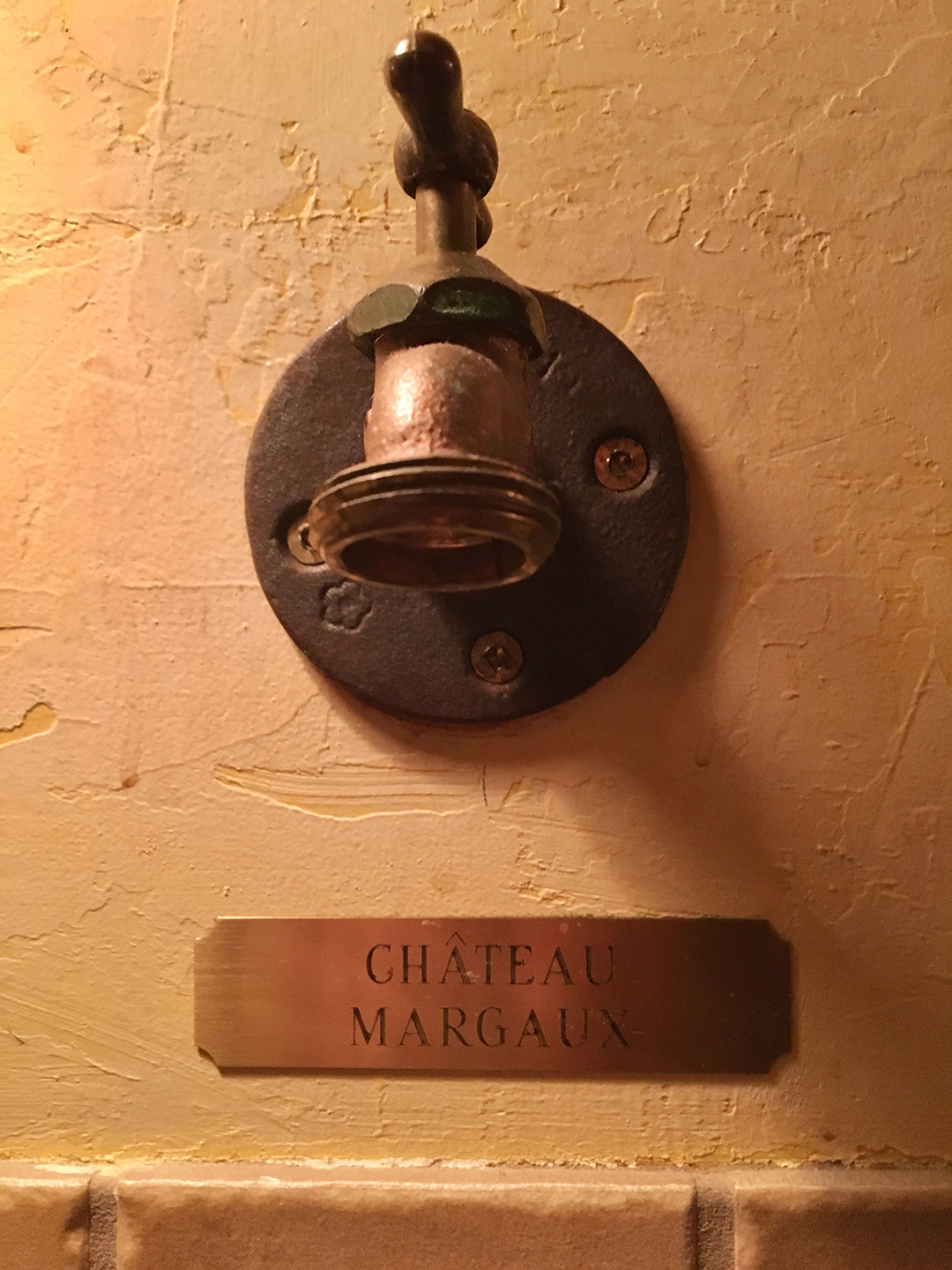 A tap with a brass plaque below is that says CHATEAU MARGAUX