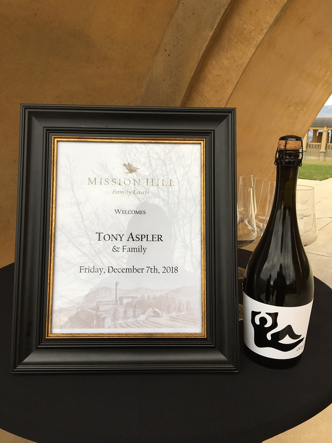 Framed paper on a table next to a bottle of wine: Mission Hill Family Estate welcomes Tony Aspler & Family, Friday, December 7th, 2018