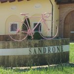 Sandrone sign made to look like a part of a barrel with SANDRONE on the metal; on the top edge of the barrel piece, a bicycle painted completely pink