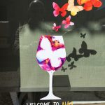 "Window with a painting of a wine glass with butterflies coming out of it and the text below ""WELCOME TO ALBA We make you fly!"""