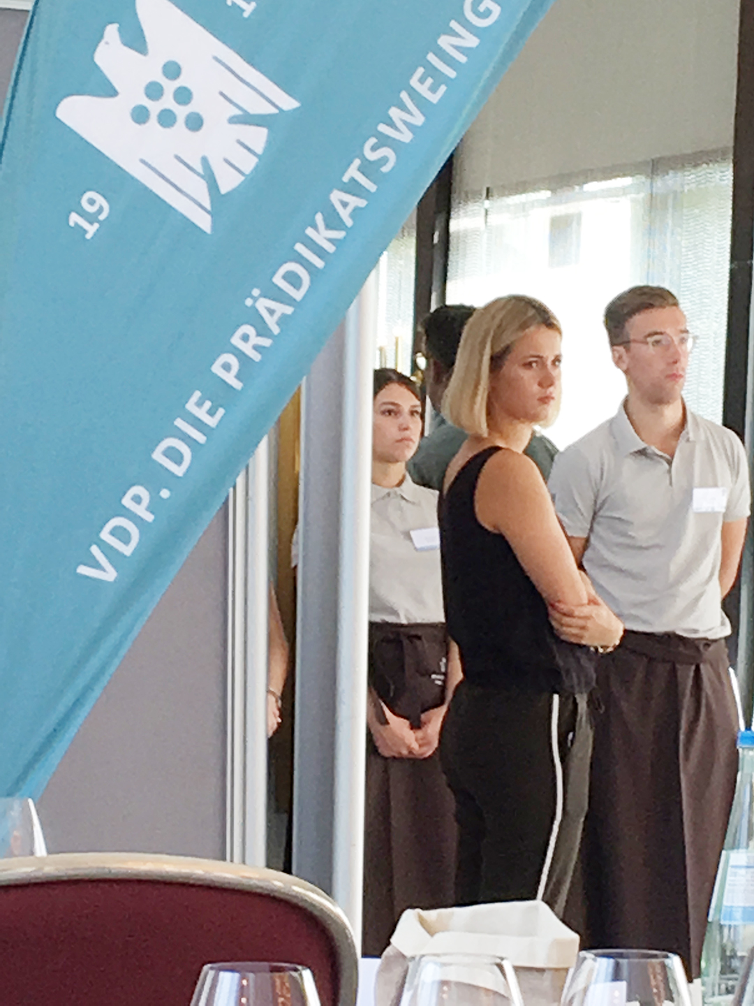 Good-looking young serving staff seen in a doorway behind a light blue banner reading 'VDP. DIE PRÄDIKATSWEING…'
